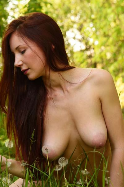 Redhead beauty Eva M showcases her amazing body outdoors