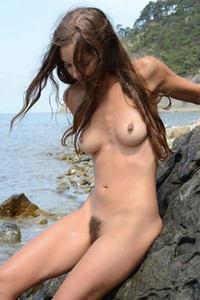 Petite babe Geissa is naked and wet on the seashore