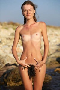 Claudia gets naked and poses erotically on the beach
