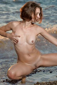 Dazzling babe Oda stretches and poses on the beach