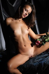 Nastia covers her small puffy breasts with a red rose