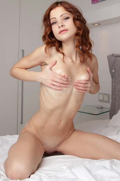 Petite Emanuelle showcases her small puffy breasts on the bed