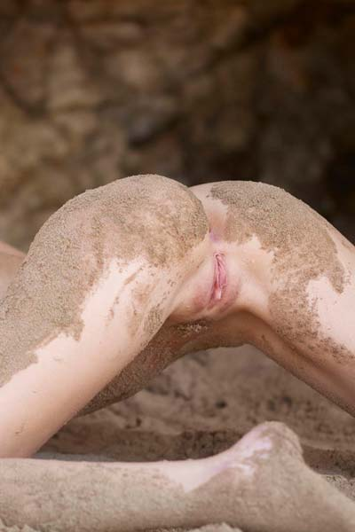 Katia covers her nude body with sand