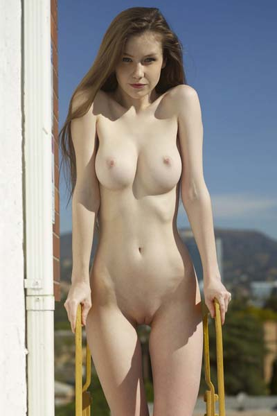 Enticing Emily Bloom posing nude on a rooftop