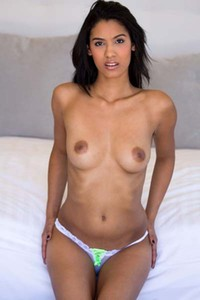 Tanned curvy babe Karmen Bella poses on the bed