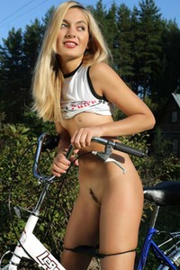 Busty blonde Lilya exposes her fantastic attributes after riding her bike