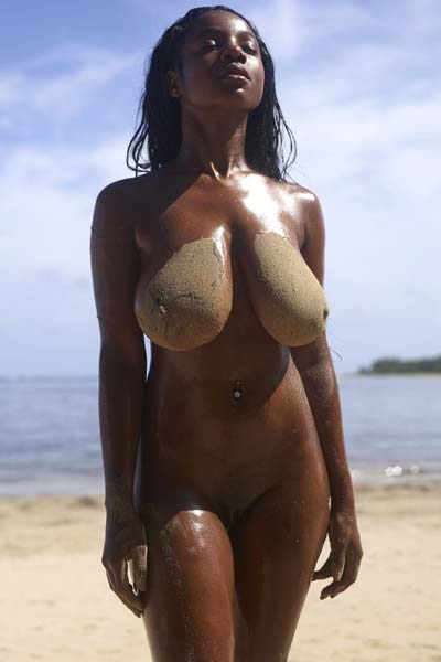 Fascinating Ebony babe Kiky flaunts her sand covered busty body