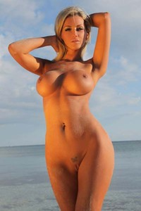Blonde fox Holly poses naked on the sandy beach and shows her beautiful naked sensual body