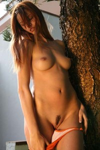 Young redhead Camille steps in the nude and poses outdoors