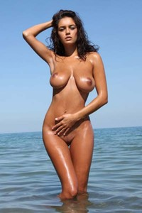 Naughty curvy babe Ela undresses and dips her sexy body in the sea
