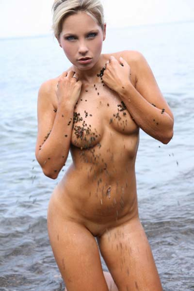 Adorable Jenni C cools down her hot body by dipping it in the sea