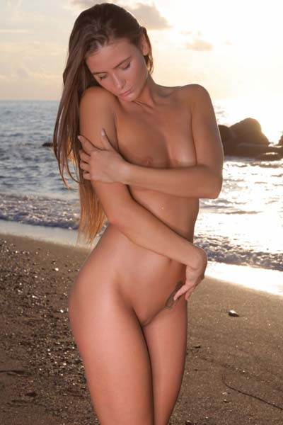 Sensual brunette Juliette falunts her sexy curves on a sandy beach