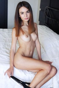 Debora A spreads her legs and shows her pink snatch while sitting on the bed