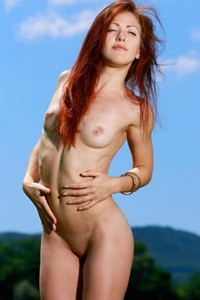 Gorgeous redhead Callista Simon disrobes her dress and presents her sexy thin waist and perky boobs