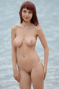 Busty redhead babe Alma poses naked on the beach and shows her hot curves