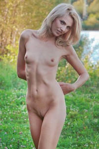 Slim and flirty blonde babe Lilly A poses seductively outdoor and displays her tight body
