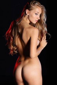 Mesmerizing blonde doll Ellison G poses in a dark and shows of her seductive body