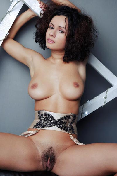 Curly haired brunette wears nothing but a garter belt posing on the sofa