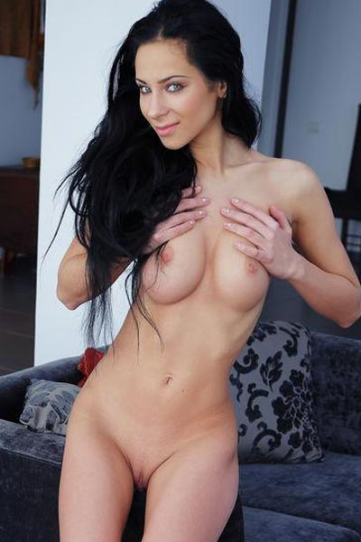 Black haired beauty relaxes on the sofa while completely and utterly nude