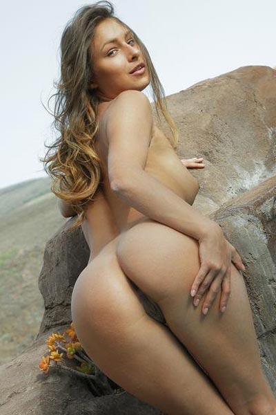 Gorgeous tanned brunette poses nude out in nature for anyone to see