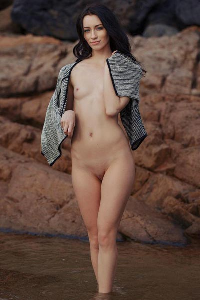 Hot brunette takes off her shirt and poses nude on a rockface