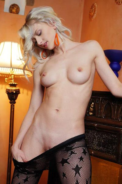 Sexy blonde in a fishnet bodysuit gently pleasures herself by the fireplace