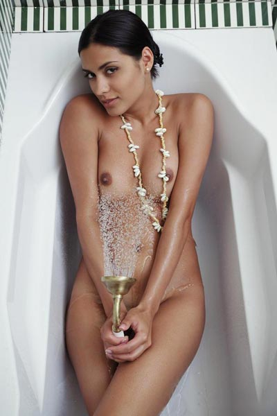 Sexy brunette lies in bathtub and uses the showerhead over her body