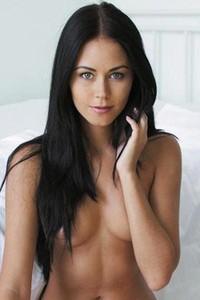 Macy B lies on bedroom floor while nude and gently pleasures herself