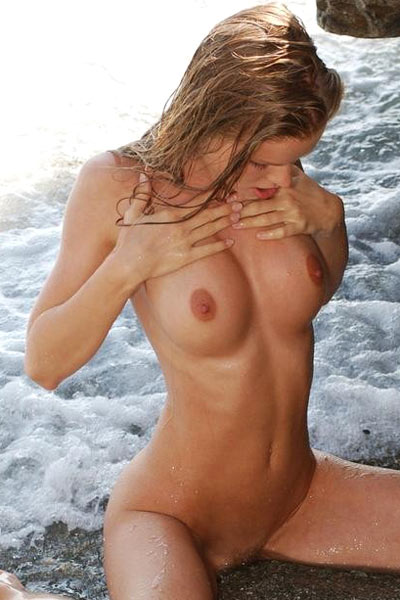 Marketa with natural firm breasts caresses her nude lean body on rocky beach