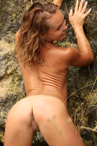 Model shows coy smile and entire nude wet body in rocky lake