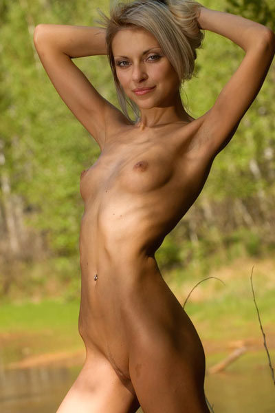 Blonde drops her blue knit dress by peaceful pond to show she is naked underneath