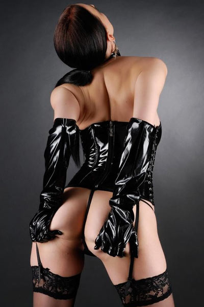 Fierce brunette in black latex dominatrix gear commands you to look