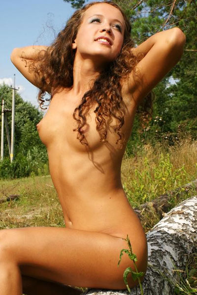 Tanned model naked in woods teases her breasts with flowers