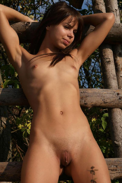 College cutie opens her lean legs wide to pose on wooden park trellis