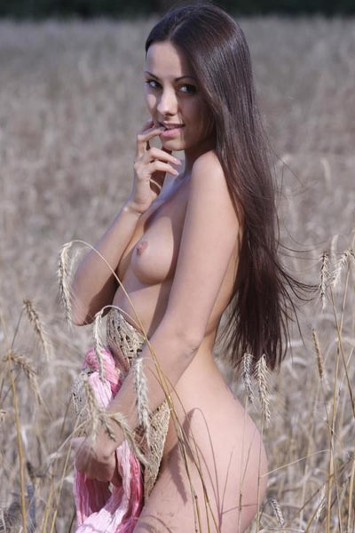 Brunette poses nude in a plantation and uses hat to cover her tasty pussy
