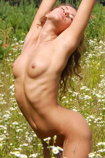 Seductive hottie archs her body and hides her pussy and ass in flowers