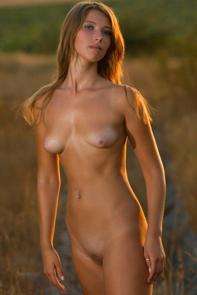 Babe with belly-button ring sits on grass and naughtily shows off her pussy