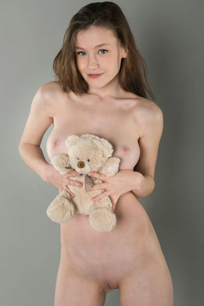 Young brunette shows off her tight body while playing with flowers
