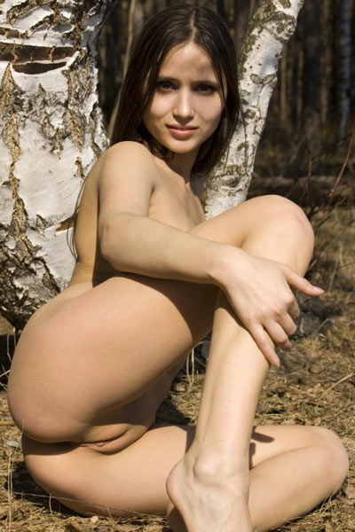 Young brunette lays naked under a tree and spreads her legs wide