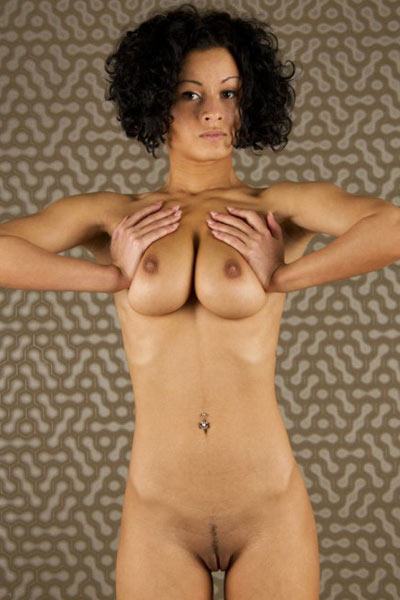 Curly haired brunette pulls down her shirt to show off her large breasts