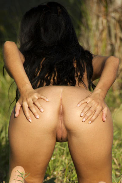 Jubia kneels while naked in the park and spreads her cheeks wide