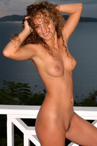 Sarka poses nude on a patio as the sun begins to set
