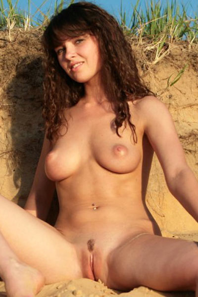 Young brunette takes off her bikini and gets into the water completely naked