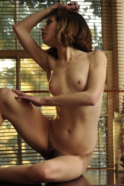 Skinny brunette sits in front of an open window and shows her naked body