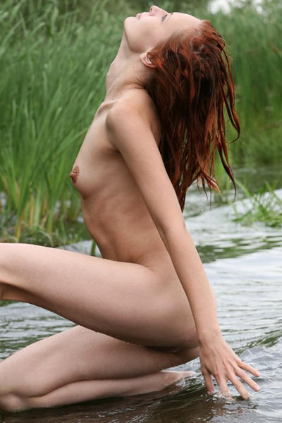 Gorgeous redhead is playng in the water while totally nude