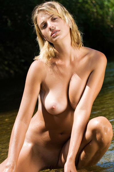 Sexy blonde with tan lines plays in the water while completely naked