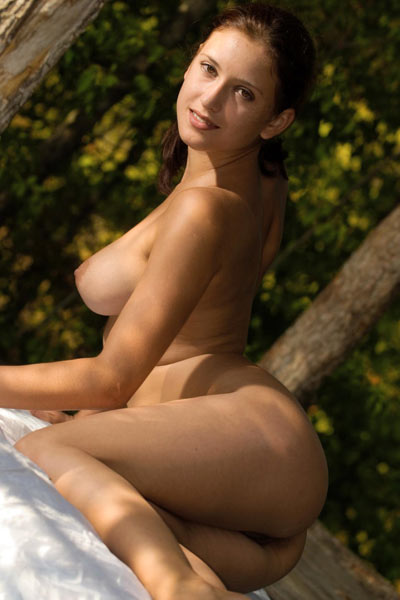 Sexy brunette squats naked in the woods and shows off her trimmed bush