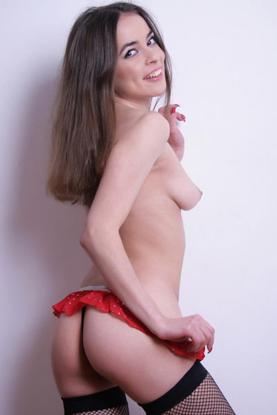 Bagira B cups her breasts with her arm while wearing just nylons