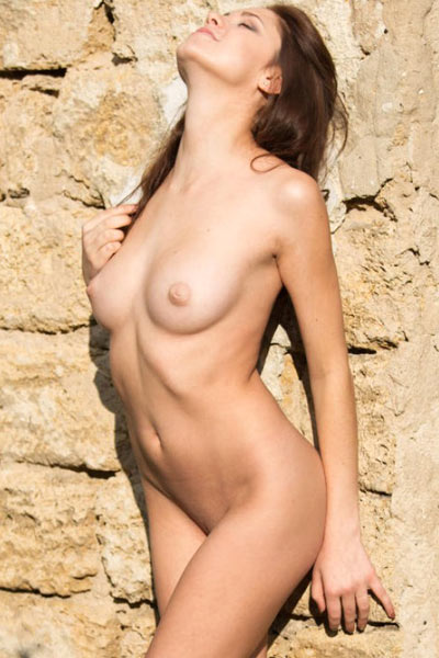 barbara Vie takes off her clothes outside and cups her small breasts