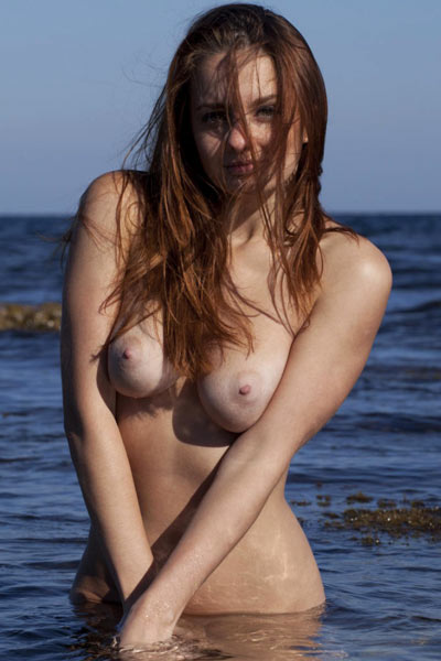 Young brunette is topless in the water showing off her sexy tan lines